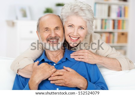 Affectionate elderly couple with beautiful beaming friendly smiles posing together in a close embrace in their living room - stock photo