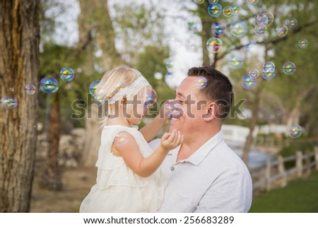 Affectionate Father Holding Cute Baby Girl Enjoying Bubbles Outside at the Park. - stock photo