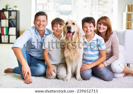 Affectionate father, mother, siblings and fluffy pet sitting on the floor - stock photo