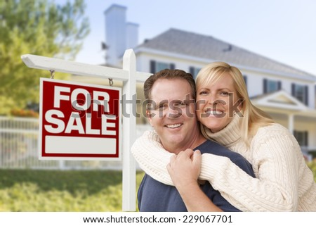 Affectionate Happy Couple in Front of New House and For Sale Real Estate Sign.