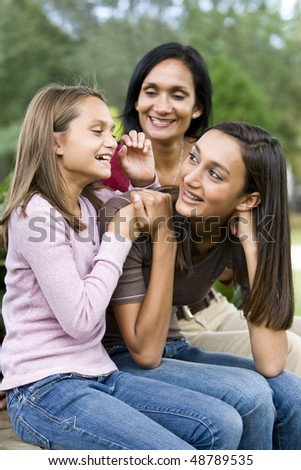 Affectionate Indian mother and two beautiful mixed-race daughters laughing together - stock photo