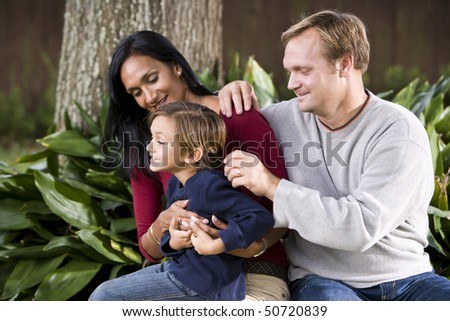 Affectionate Interracial family sitting on bench outdoors with cute five year old boy - stock photo