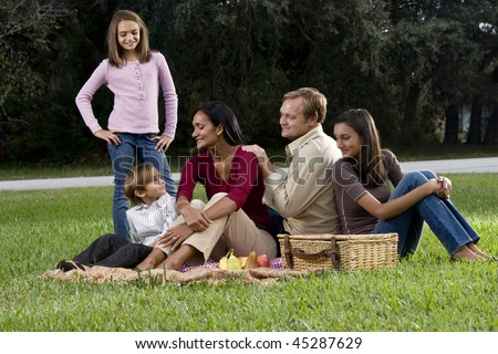 Affectionate interracial family with three children enjoying a picnic together in park - stock photo