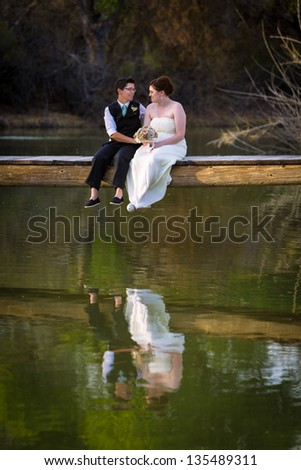 Affectionate lesbian couple sitting on dock above lake - stock photo