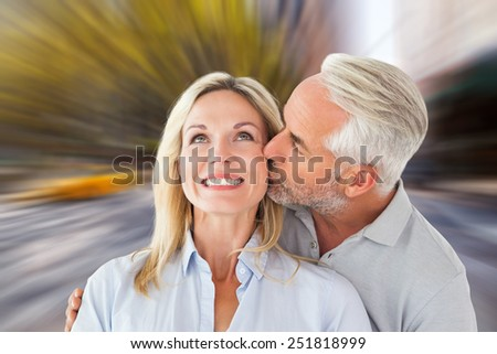 Affectionate man kissing his wife on the cheek against blurry new york street