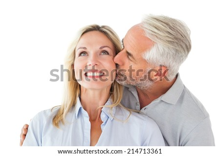 Affectionate man kissing his wife on the cheek on white background - stock photo