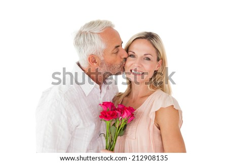 Affectionate man kissing his wife on the cheek with roses on white background - stock photo