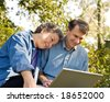 Affectionate mature couple at their laptop, outdoor setting - stock photo