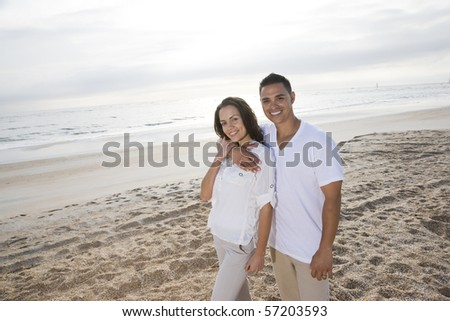 Affectionate mid-adult Hispanic couple standing on beach - stock photo