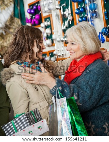 Affectionate mother and daughter with Christmas presents and shopping bags embracing at store - stock photo