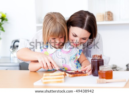 Affectionate mother helping her daughter prepare the breakfast in the kitchen - stock photo