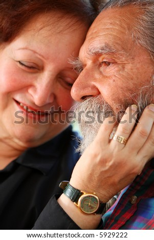 Affectionate old couple with the wife holding on lovingly to the husband's face. Focus on the husband's eyes. Concept: Elderly love. - stock photo