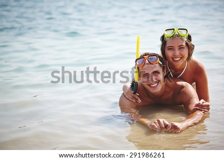 Affectionate scuba divers lying in water - stock photo
