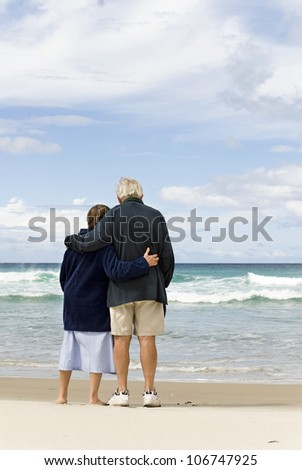 Affectionate senior couple embracing at the beach while looking out to sea - stock photo
