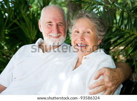Affectionate senior couple in tennis whites, against a background of tropical palm fronds. - stock photo
