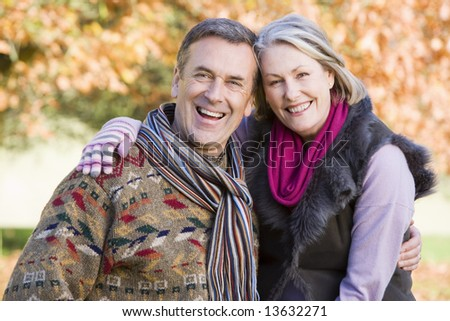 Affectionate senior couple on autumn walk with trees in background - stock photo