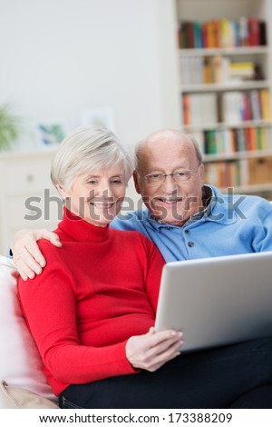 Affectionate senior couple sharing a tablet-pc sitting close together on a sofa in the living room reading information on the screen - stock photo