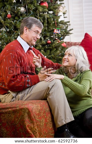Affectionate senior couple talking by Christmas tree - stock photo