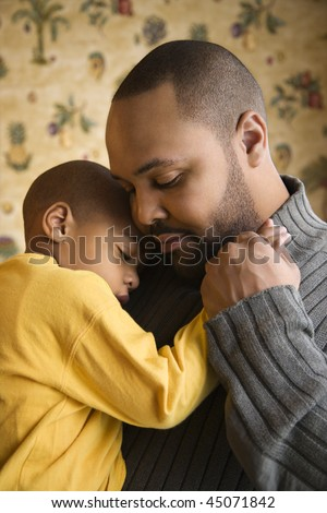 Affectionate young african-american father holds young son to his chest.  Vertical shot. - stock photo