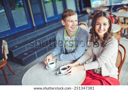 Affectionate young couple having coffee in cafe - stock photo