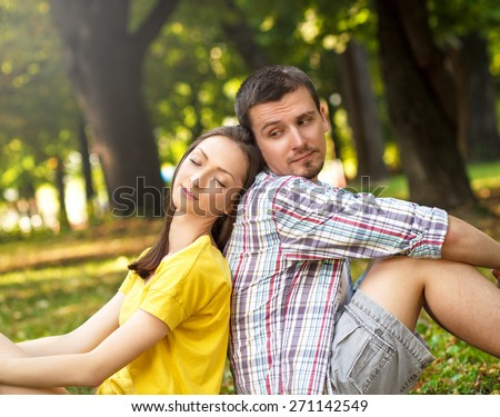 Affectionate young couple sitting in park, leaning on each other. - stock photo