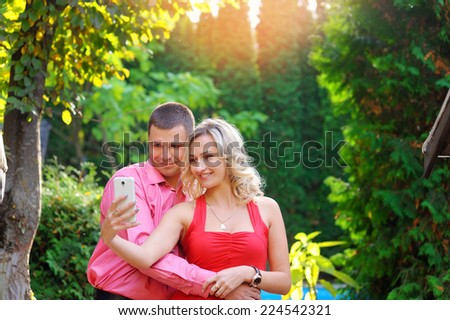 Affectionate young couple taking pictures using a smart phone at the park. Teenage boy and girl in love photographing themselves outdoors.  - stock photo