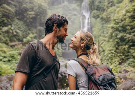 Affectionate young couple together on hike. Young man and woman with backpack looking at each other and smiling. Hiking in forest with waterfall in background.