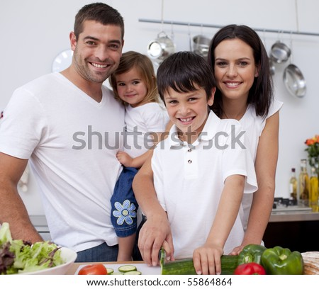 Affectionate young family cooking together in the kitchen - stock photo