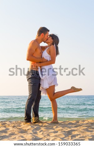 Affectionately embraced and tenderly kissing, a young couple enjoys a mid summer late afternoon, on a wet sandy beach.