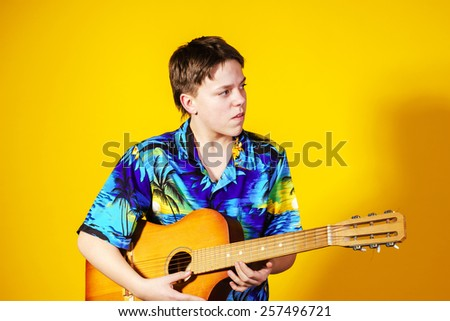 Affective teenage boy with guitar. Music concept. Isolated on yellow background - stock photo
