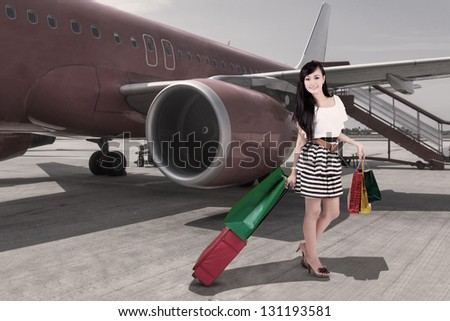 Affluent travel with beautiful woman arriving at airport - stock photo
