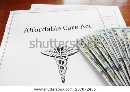 Affordable Care Act insurance papers with cash                                - stock photo