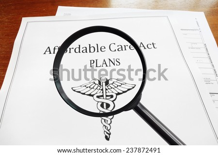 Affordable Care Act Plans document and magnifying glass                                - stock photo