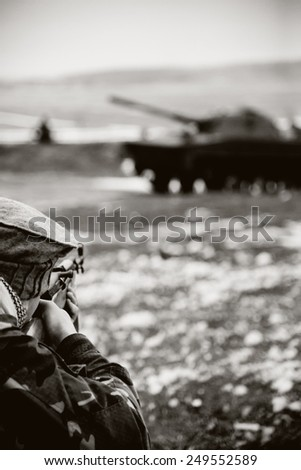 Afghan soldier in action shooting enemy from a rifle. Retro color - stock photo