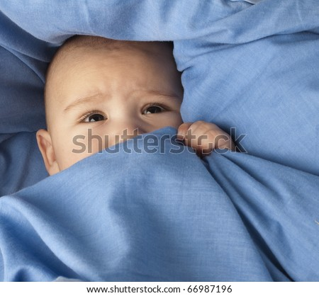 afraid baby under a blue blanket closeup - stock photo