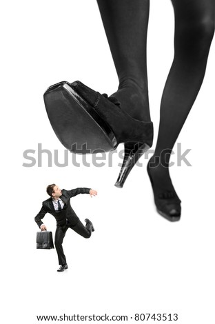 Afraid businessman running away from a big foot isolated on white background - stock photo