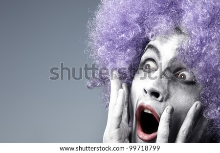 Afraid clown on a blue background - stock photo