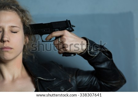 Afraid despair woman with gun committing suicide - stock photo