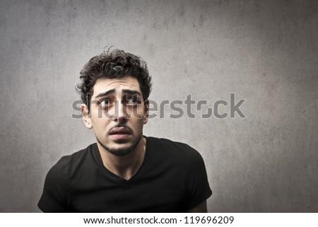 Afraid guy in black - stock photo