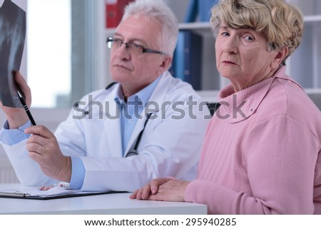 Afraid older woman during visit at doctor's office - stock photo
