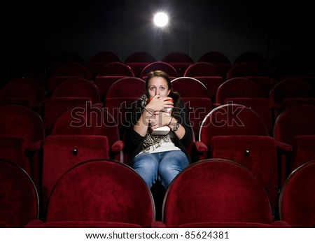 Afraid young woman alone in the movie theater - stock photo