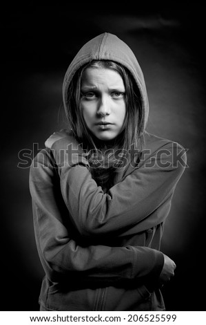 Afraided, sad teen girl in hood - stock photo