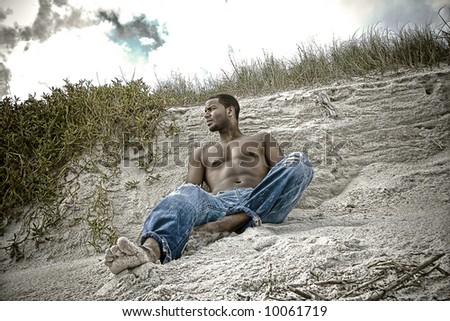 Afrcian American man sitting on a beach - stock photo