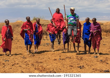 AFRICA, KENYA, MASAI MARA - SETPEMBER 10: Masai warriors show traditional dance jumps to a tourist near Masai Mara National Park Reserve, September 10,2013,Kenya - stock photo