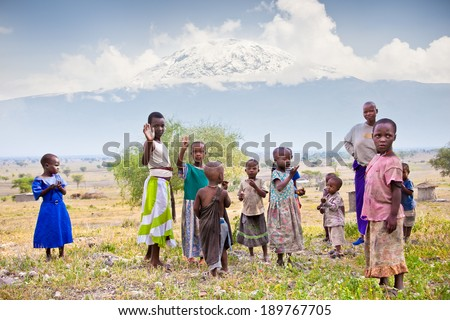 AFRICA, TANZANIA-FEBRUARY 9, 2014: Portrait on an African Kids of Masai  tribe village smiling to the camera,  living in house made with cow dung , February 9, 2014. Tanzania. - stock photo