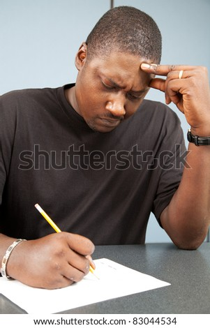 African-american adult education student struggles with test anxiety as he takes an exam. - stock photo