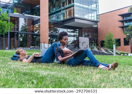 African American and Caucasian female students lying on grass studying with laptop computers - stock photo