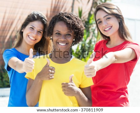 African american and caucasian girlfriends in colorful shirts showing thumbs - stock photo