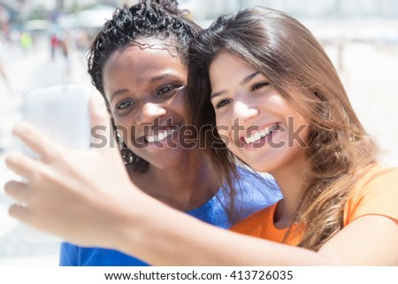 African american and caucasian girls taking photo outdoor in the city with buildings in the background
