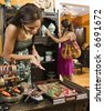 African American and Indian women shopping  in boutique. - stock photo